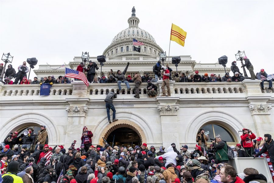 Rioters gather and climb the Capitol's walls. (Photo credit: Lev Radin)