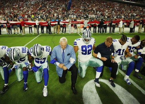 The Dallas Cowboys kneel during the national anthem before a game.